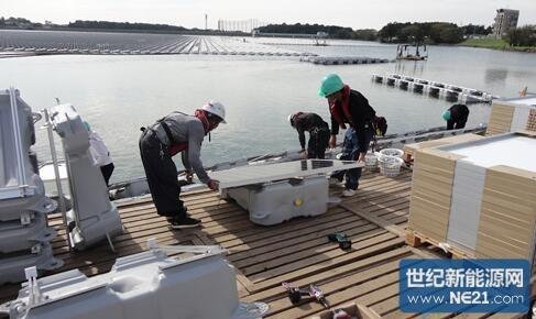在湖畔的作业场将太阳能电池板装在浮体架台上